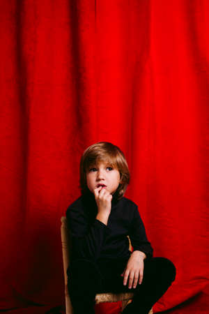 Five years old thoughtful boy with his hands on the mouth, against a red curtain