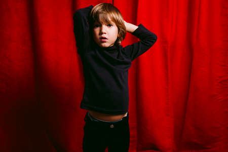Three years old boy, wearing black clothes, crying against a red curtain