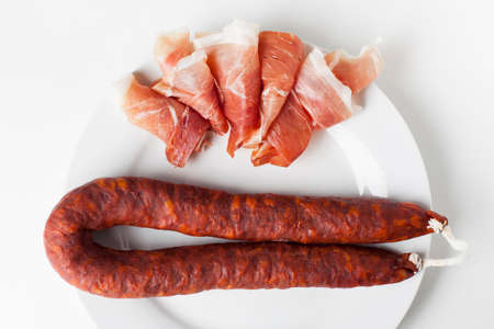Spanish ham and a chorizo sausage on a white plate Banque d'images