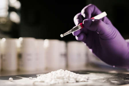 Hands of a scientist working with some pills