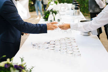 Waiter giving a cup of coffee to an atendee during a coffee break