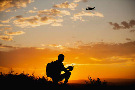 Silhouette of a young man with a backpack operating a drone in A Rural Setting on sunset Stock fotó