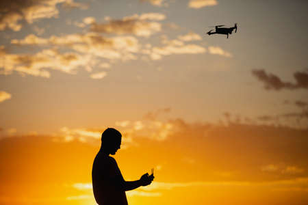 Silhouette of a young man operating a drone in A Rural Setting on sunset Stock fotó