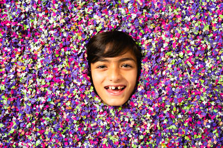 Surprised Young boy face blowing a party horn being surrounded by colored confetti