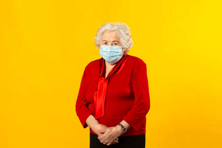 Studio portrait of a senior woman wearing a red shirt and a surgical facial mask, against a yellow background