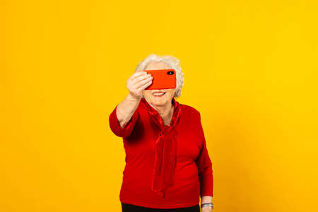 Studio portrait of a senior woman wearing a red shirt against a yellow background and having a video call with a red mobile phone