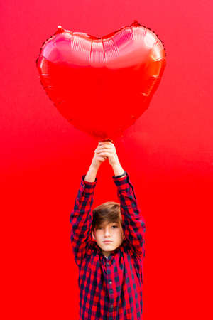 Boy holding a big red heart shaped balloon against a red wall