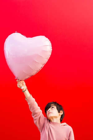 Boy holding a big pink heart shaped balloon against a red wall Stock fotó