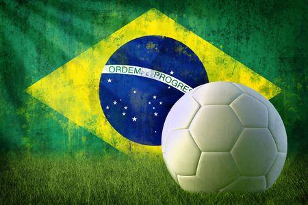 Grunge brazil flag on wall and soccer ball photo