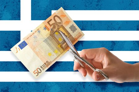 Hand cut euro banknote on greek flags background