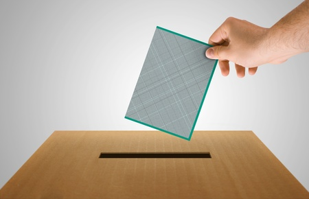 Human hand insert the electoral document on urn for voting