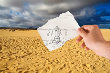 hand holds paper with sketch the fontanelle of water in the middle of the desert