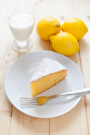 Slice of lemon cake in a dish on wood table