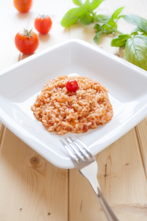 risotto: Dish of tomatoes risotto on wood table