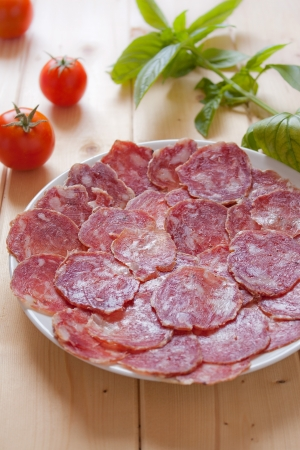 cold cuts: Dish of seasoned sausage slices on the wood table Stock Photo