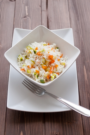 Basmati rice with carrots and courgettes in a dish on wood table