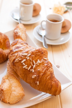 Assorted sweet brioches on dish and hot coffee morning breakfast photo