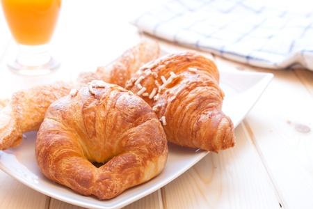Assortiment de brioches sucrées sur le plat et jus de fruits pour le petit déjeuner le matin Banque d'images