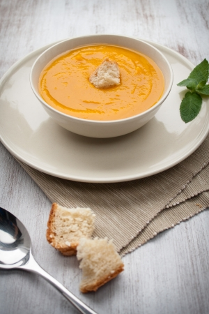 Bowl of pumpkin soup with bread crouton on white wood table