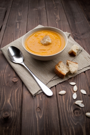pumpkin soup: Bowl of pumpkin soup with bread crouton on white wood table