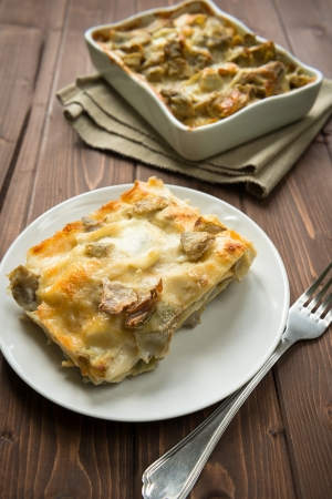 Dish of Lasagna with artichokes on wood table