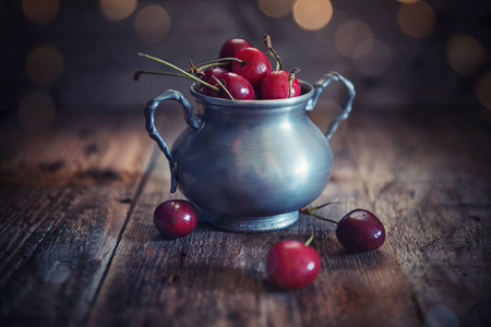 Cup of cherries on wooden rustic background