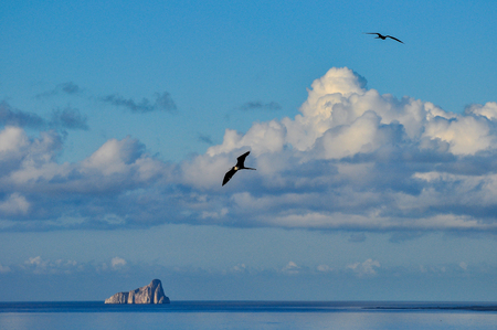 The sleeping lion rock off the coast of San Cristobal Island with a frigatebird flying in the sky.