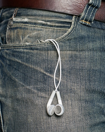 Headphones hanging off a jeans pocket