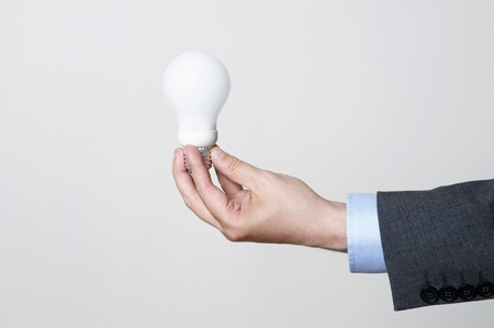 Man in a suit holding a light bulb