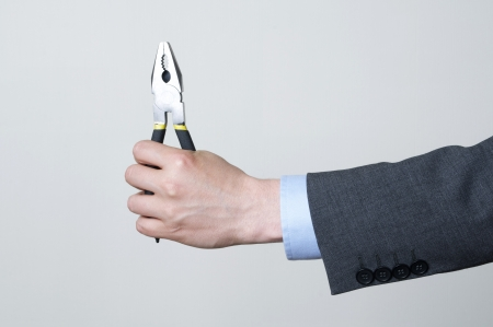 A man in a suit holding a tool