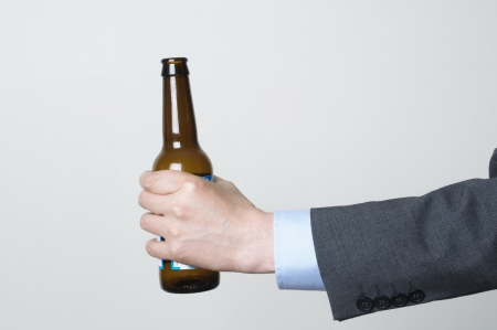 Man in a suit holding a beer bottle Stock Photo