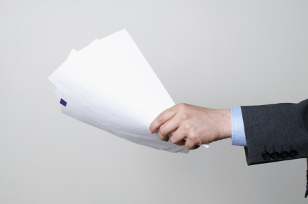 man in a suit holding some papers photo