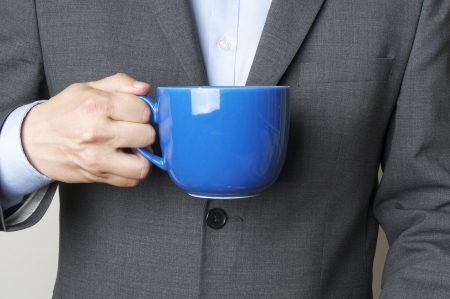 Man in a suit holding a cup