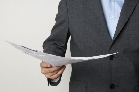 man in a suit holding some papers