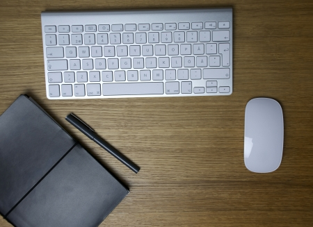 A desk with a keyboard, notebook, pen and a mouse Stock Photo - 14297784