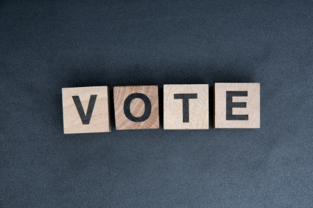 e survey: Wooden cubes with letters, spelling vote. Stock Photo