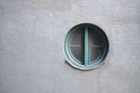 Round window on a blank grey wall Stock Photo - 16417719