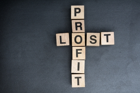 finance a helping hand confusion: Wooden cubes spelling profit lost