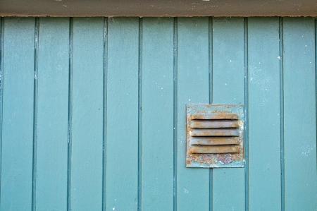 Old green wooden panel with a ventilator Stock Photo