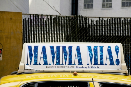 Yellow taxi cab in New York with a Mamma Mia sign