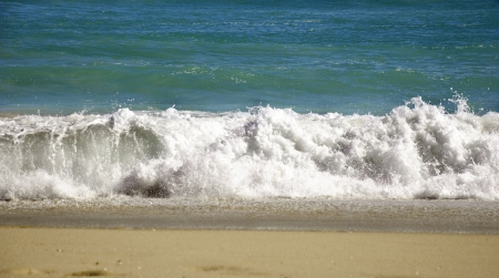 a wave on a sandy beach comes to shore. Stock Photo