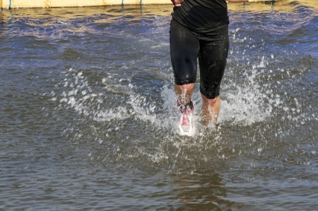 Person running in water Stock Photo