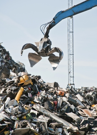 Scrap metal, iron and computer dump with crane. photo