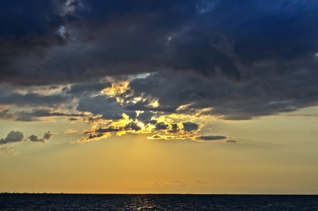 Sunset over large body of water with rays of light coming through clouds Stock Photo