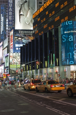 People and taxies at Times Square during night time.