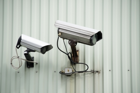 Two surveillance cameras on industrial wall