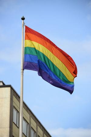 Large rainbow flag proudly waving against the blue sunny skies Stock Photo
