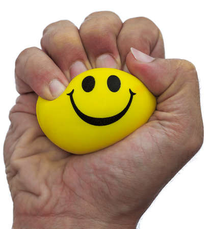 front view of a hand squeezing tightly a yellow stress ball with happy face