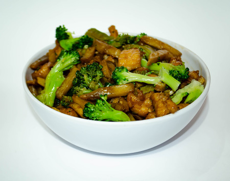 Chicken, sliced ??potatoes and broccoli are spiced in a white bowl on this delicious typical china dish, this image is good for oriental restaurants, snack bars and any establishment in the food business. Banco de Imagens