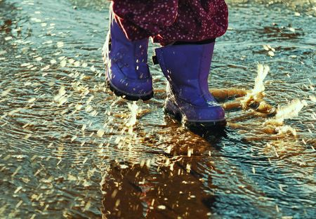 rainy day: Purple boots splashing in puddles